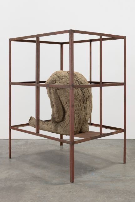 Sculpture of a life-size seated burlap and resin figure in an iron cage by Magdalena Abakanowicz