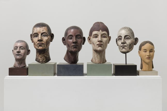 Group of six different sculptural heads ranging in size, gender and color