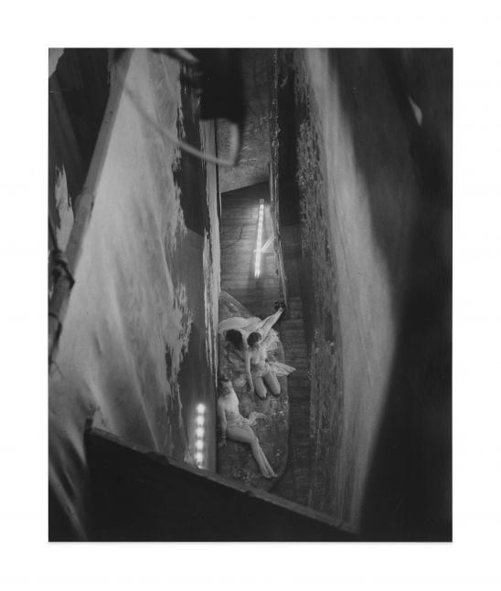 Black and white gelatin silver print depicting a birds eye view of three angelic naked women on stage.