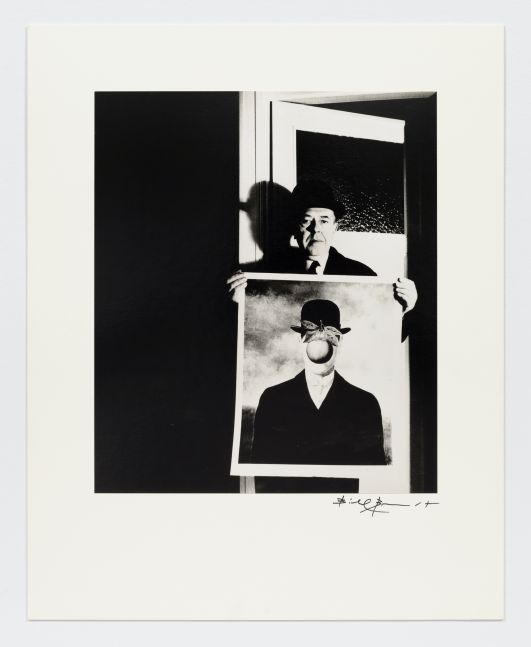 "Black and white photographic portrait of man holding Magritte's ""The Son of Man"" by Bill Brandt."