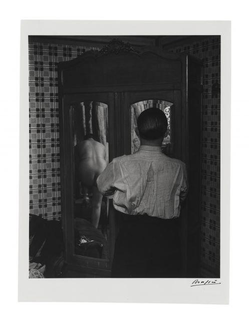 Black and white silver gelatin print of man looking into mirrored wardrobe in a brothel by Brassaï