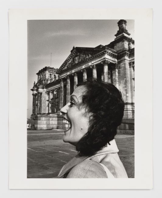 Black and white photographic print by Helmut Newton featuring the profile view of a woman laughing near the Reichstag