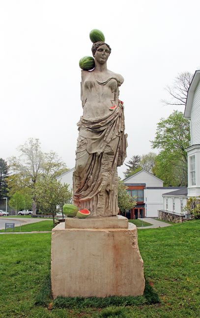 Outdoor installation shot of a cast stone, bronze and steel sculpture of the goddess Hera by Tony Matelli with hyper-realistic watermelons spread throughout