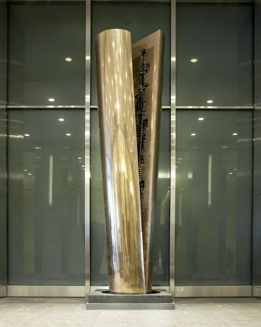 Outdoor installation view featuring a bronze sculpture by Arnaldo Pomodoro of a split column
