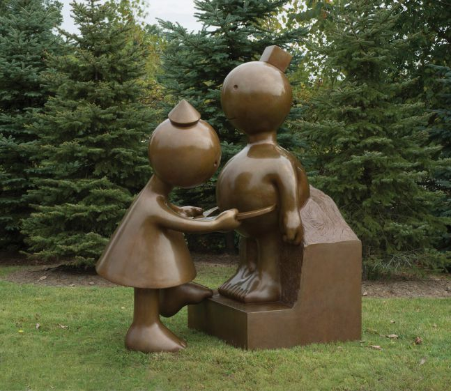 Installation shot of Tom Otterness' sculpture of a dressed figure measuring another figure atop a small pedestal.