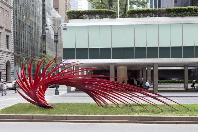 An installation shot of Santiago Calatrava's sharp, red, and angular stainless steel sculpture sits atop grass on Park Avenue.