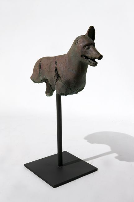 Rusted and fragmented bronze dog statue atop a steel rod.