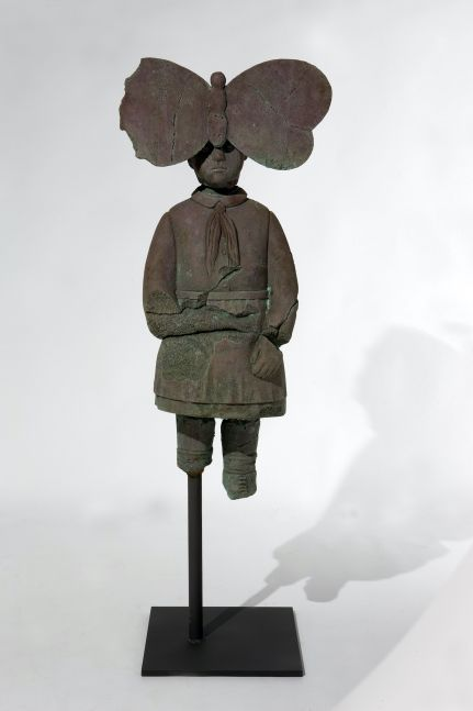 Rusted and fragmented bronze statue of young girl with large butterfly on forehead by Grisha Bruskin.