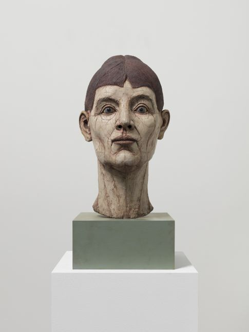 Resin, fiberglass, stone dust and acrylic sculptural head of figure with short brown hair and blue eyes