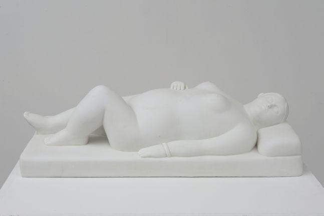 White marble sculpture of a reclining woman on pillow.