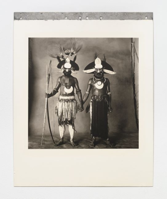Black and white double portrait of two New Guinea warriors holding hands.