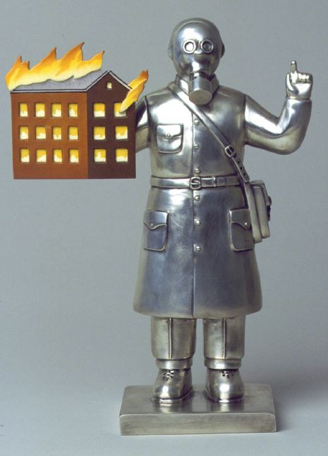 Stainless steel statue of a character with a gas mask and a model of a burning house.