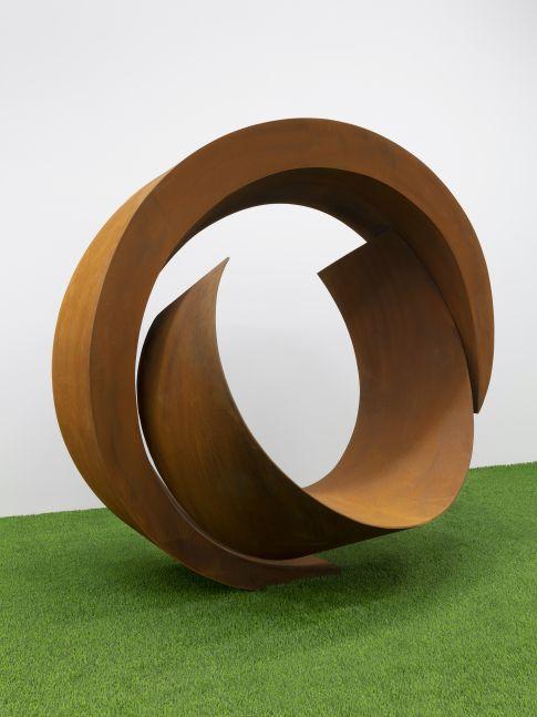 Steel circular abstract sculpture with burnt orange hue by Beverley Pepper.