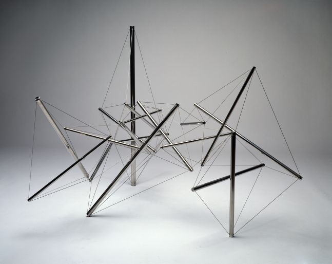 Web of stainless steel cylinders held together with wire in angular formation.