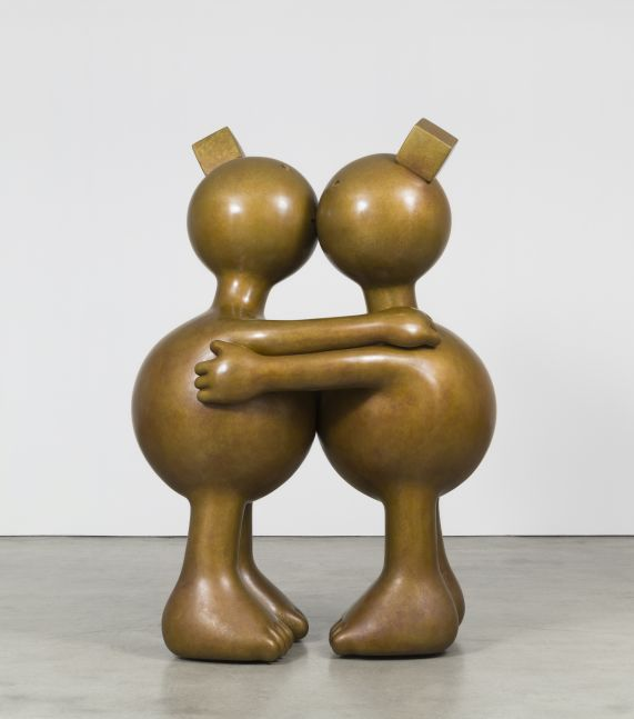 Two large bronze and rotund sculptures kissing by Tom Otterness.
