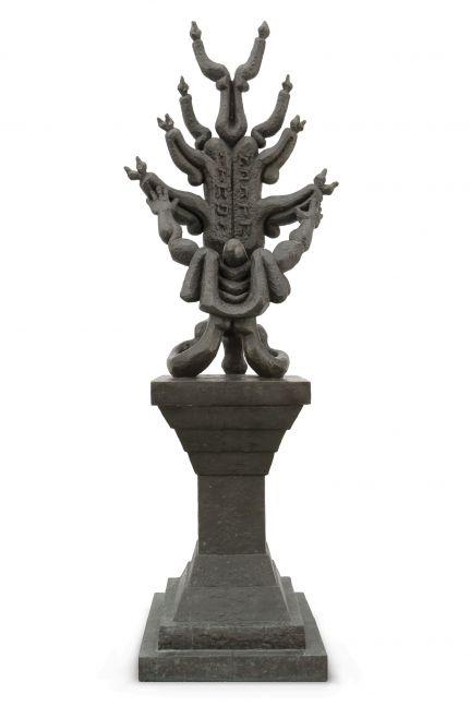 Bronze sculpture with praying figurine atop pedestal.