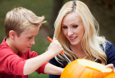 Kid carving pumpkin with mom