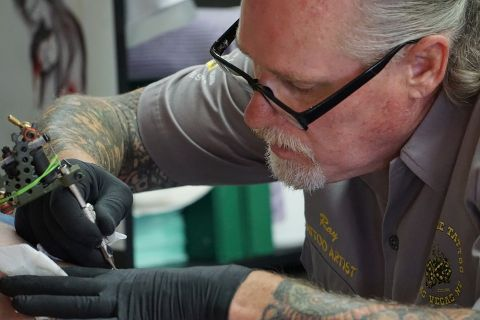 Image of a tattoo artist doing tattoo work