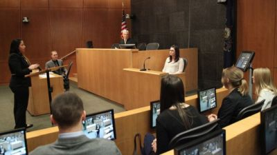 Picture of courtroom - person on the stand giving her testimony