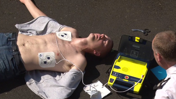 Using AED for rapid defibrillation on person needing help