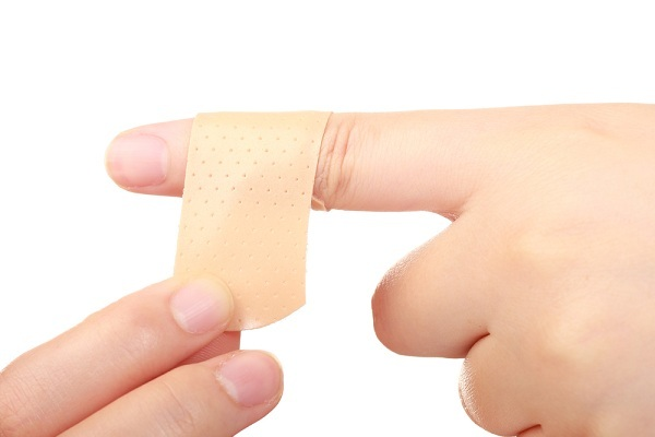 putting band aid on finger