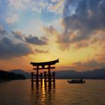 Miyajima Torii silhouette at dusk with cruising boat.