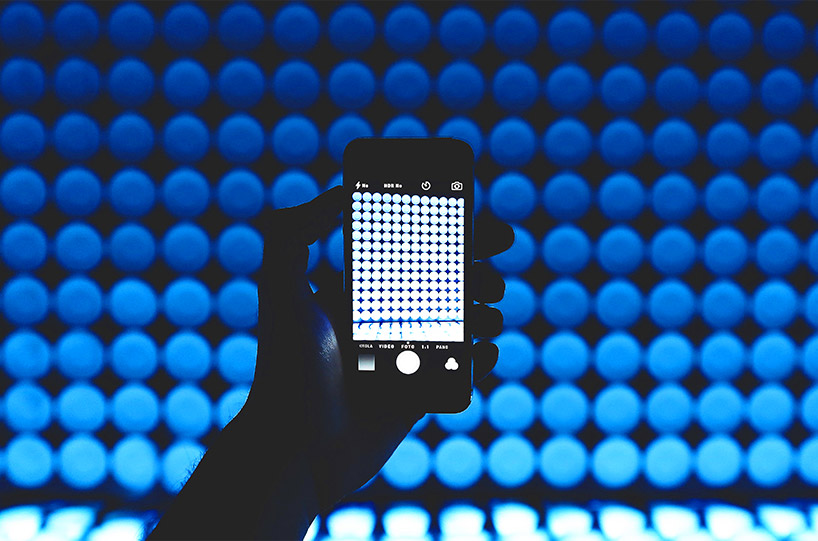 Image of a hand holding up a cellphone in a dark room with blue lights in the background.