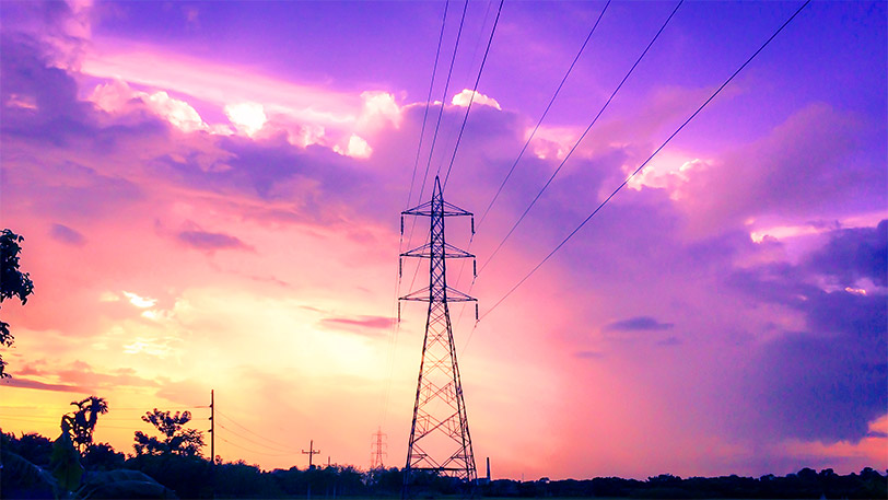 Image of a powerline tower against a purple and yellow sunset.