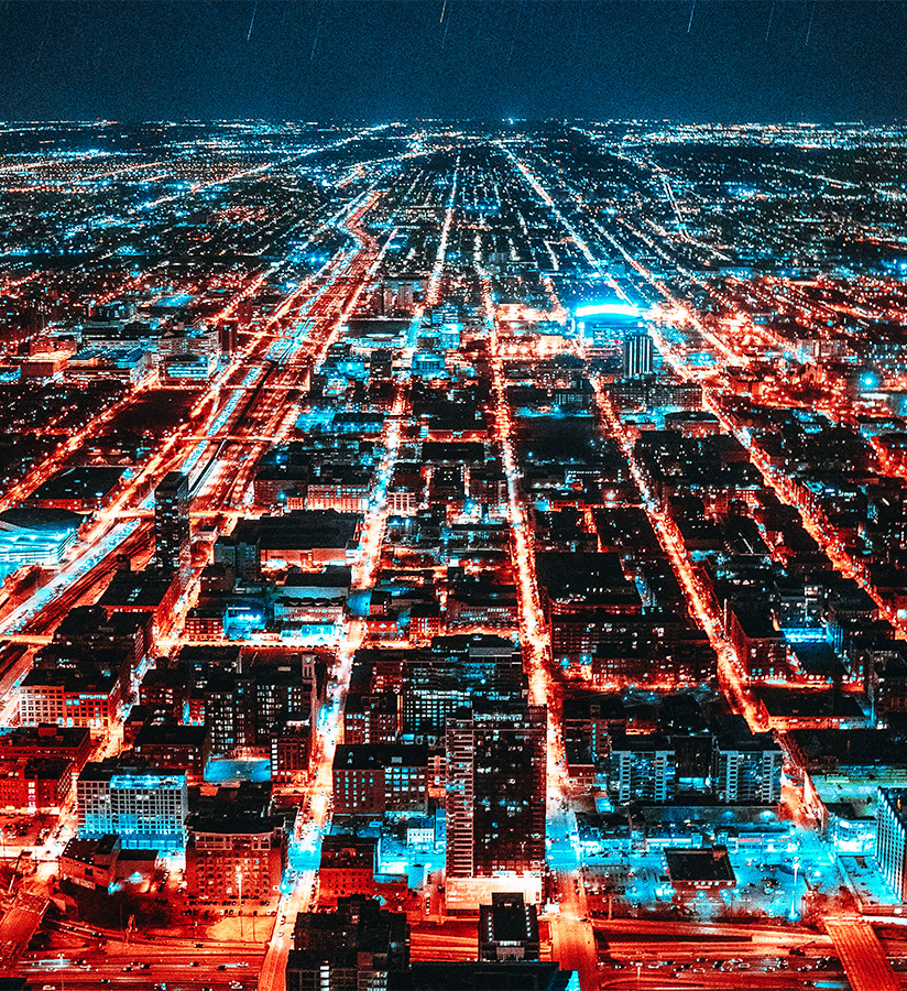 Aerial view of a large city at night with the lights of the streets and buildings tinted red and blue.