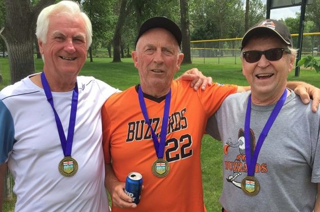 Buzzards' manager Erv Krawchuk, left, catcher Rod Gaus and pitcher Brian 'Buck' Kupsch are in a celebratory mood after their team's gold medal win in the men's 70-plus category at the Alberta 55 Plus Summer Games