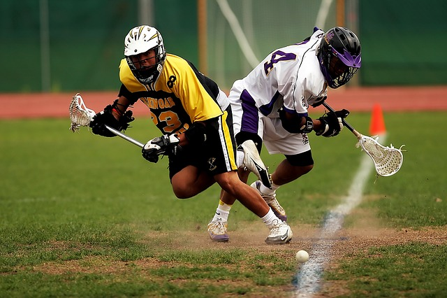 two lacrosse players on field