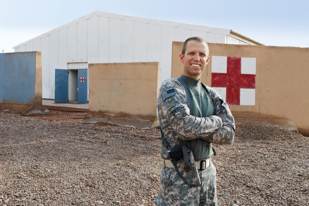 Major Dan Johnston, MD, poses at Iraq's Camp Taji, a sprawling airbase located about 12 miles from Baghdad. Dan works to maintain medical readiness of a 2,600- member aviation unit, flight crews and maintenance and support staff.  He oversees a team of six doctors, five physician assistants and more than 20 medics being spread throughout Iraq.