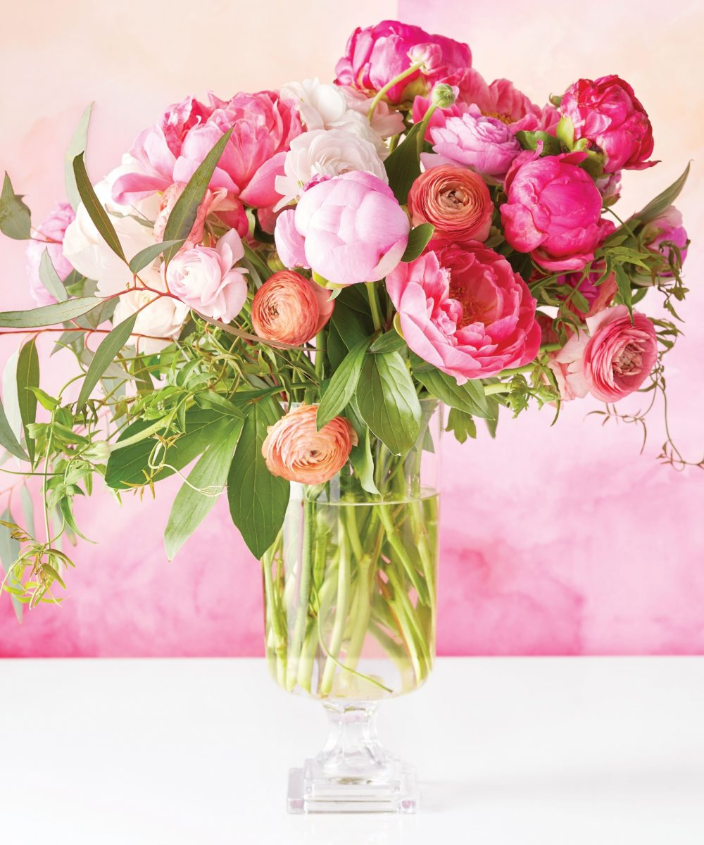 Peonies, Ranunculus, Ivy & Snow Gum Eucalyptus in a footed glass vase