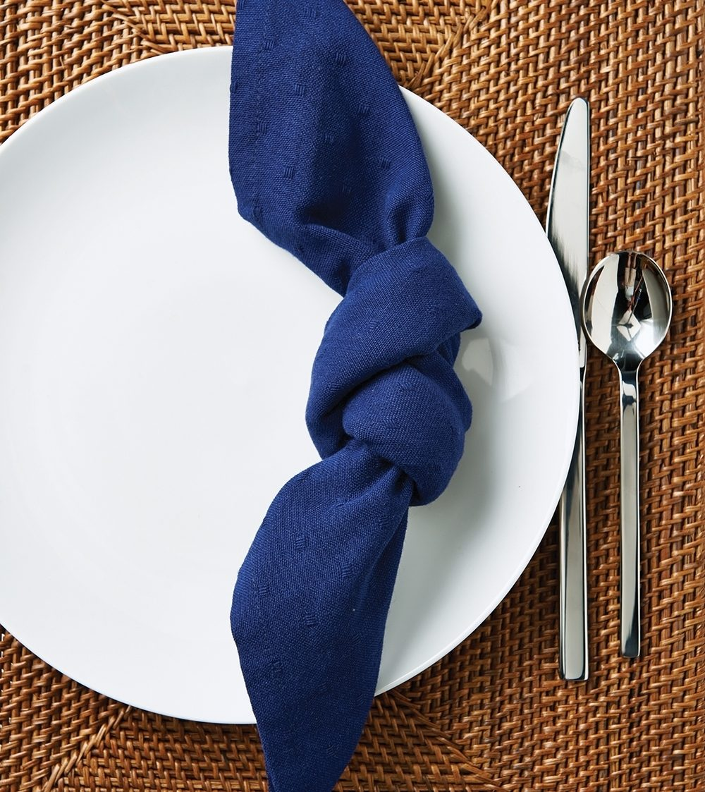 knotted napkin on a plate with silverware