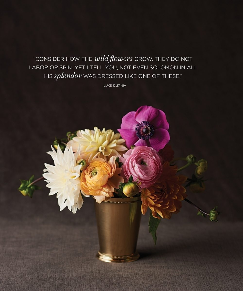 A bouquet of dahlias, ranunculus, and a poppy in a small gold vase with the Bible verse Luke 12:27