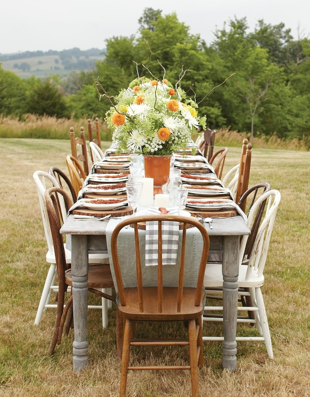 A table is set with mismatched vintage chairs and dinnerware for a casual outdoor fall party.