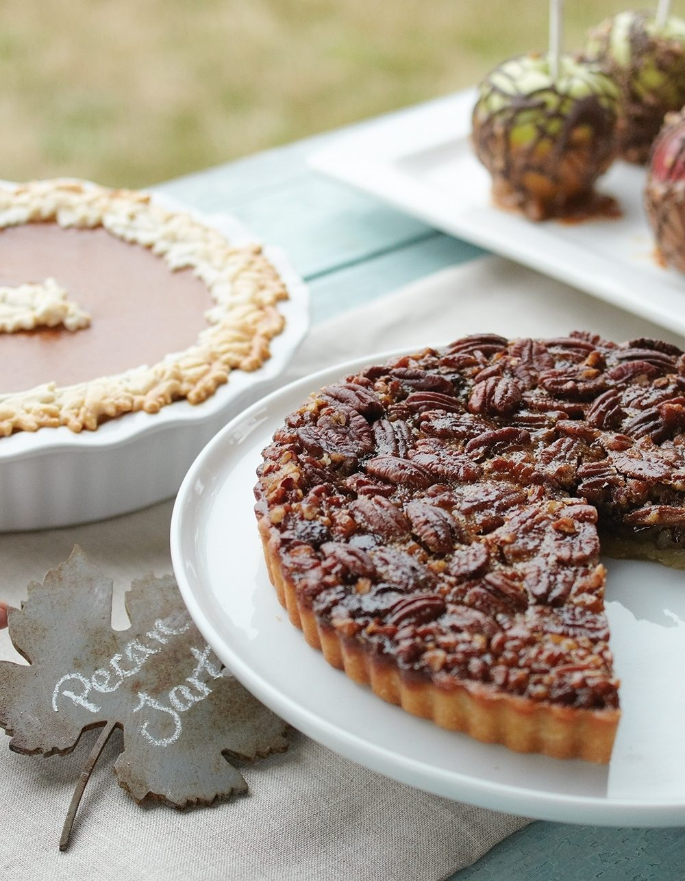 A favorite homemade pumpkin pie recipe edged with leaves made out of pie crust and a purchased chocolate pecan tart promise sweet delight at a casual outdoor fall party.