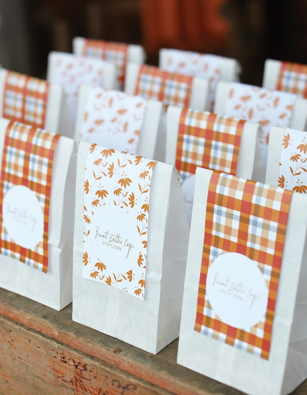 Peanut Butter Cup Popcorn is served in decorated bags on a treat table at a casual outdoor fall party.