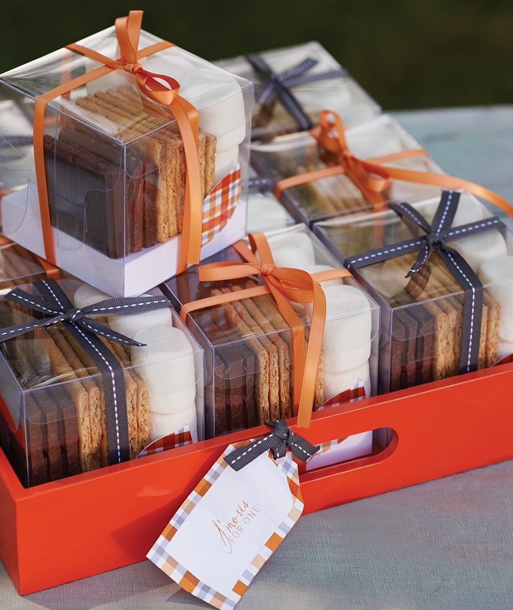 Ingredients for s'mores are divided into individually portioned boxes for guests at a casual outdoor fall party.