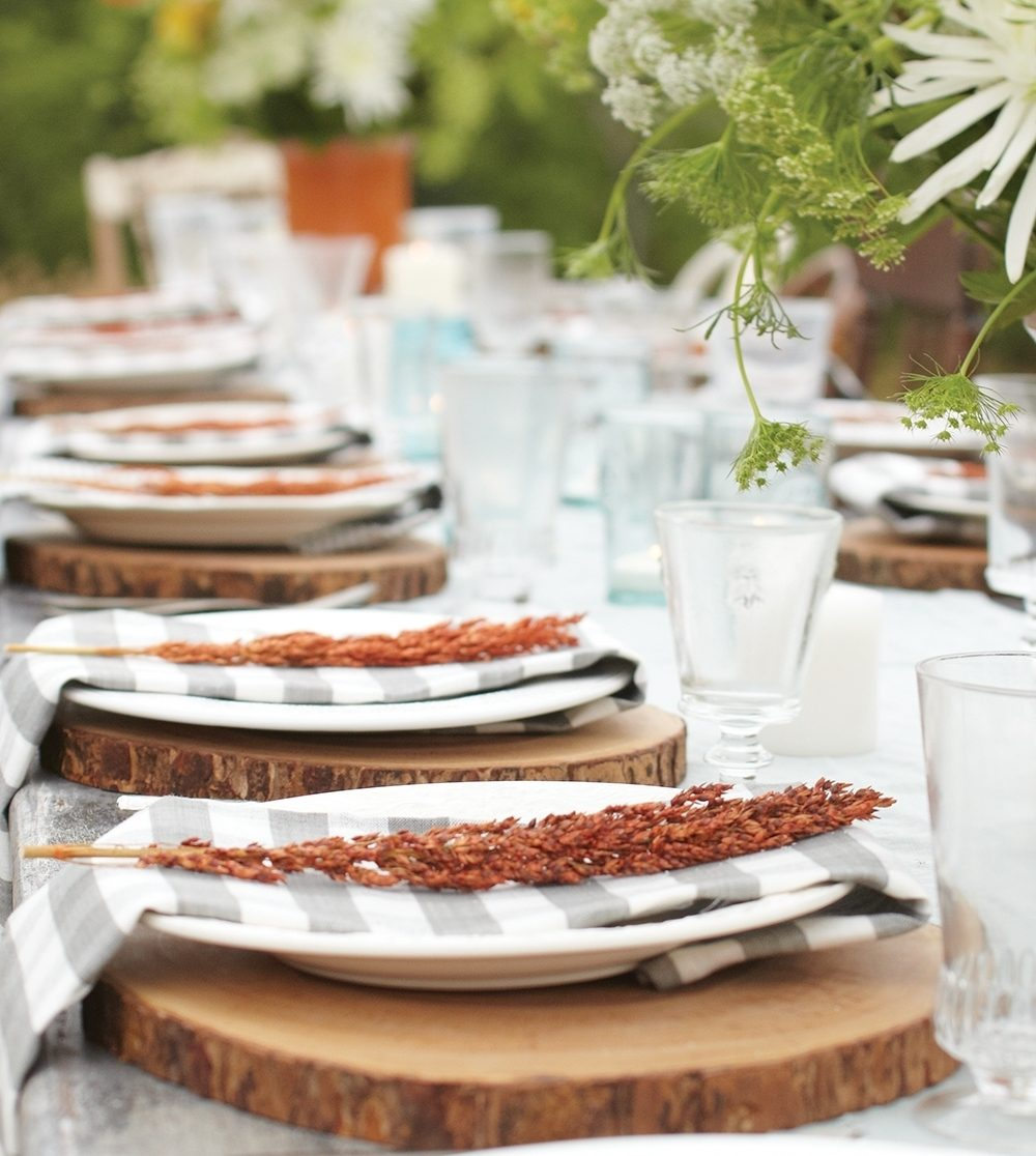Slabs from tree trunks make rustic chargers, while dish towel napkins and mismatched dinnerware keep a fall party simple and inexpensive.