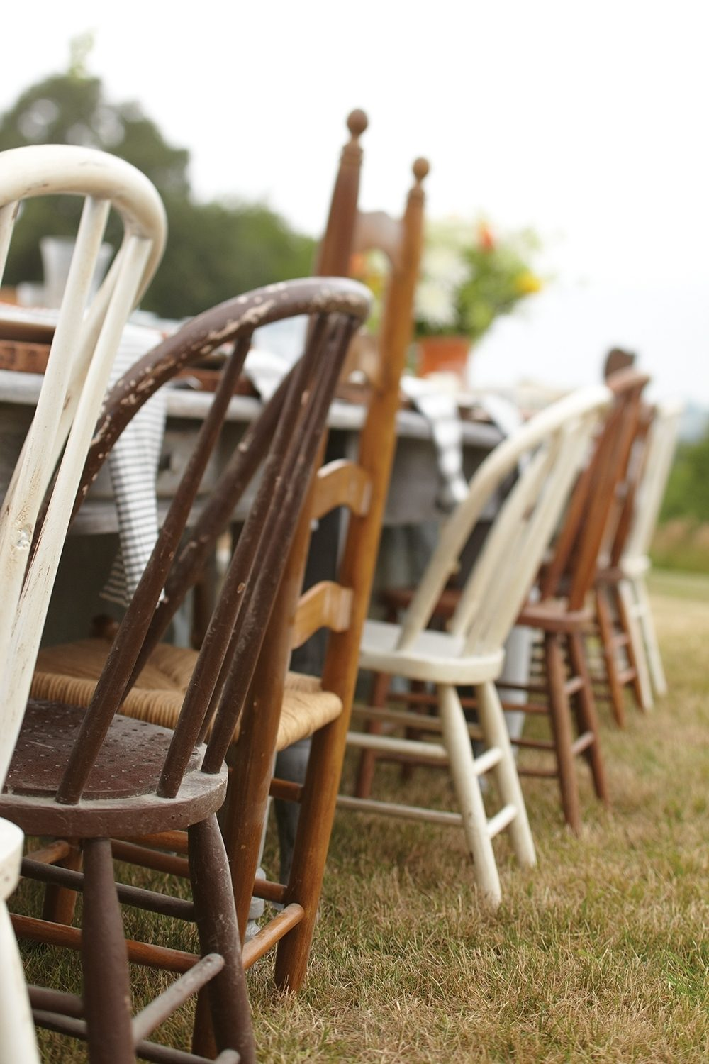 An eclectic mix of chairs gathered over the years gives seats to every guest at a casual outdoor fall party.