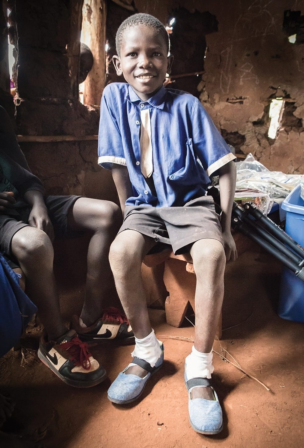 John, a Ugandan child, sports shoes from the nonprofit Sole Hope, which help him avoid jigger infections.