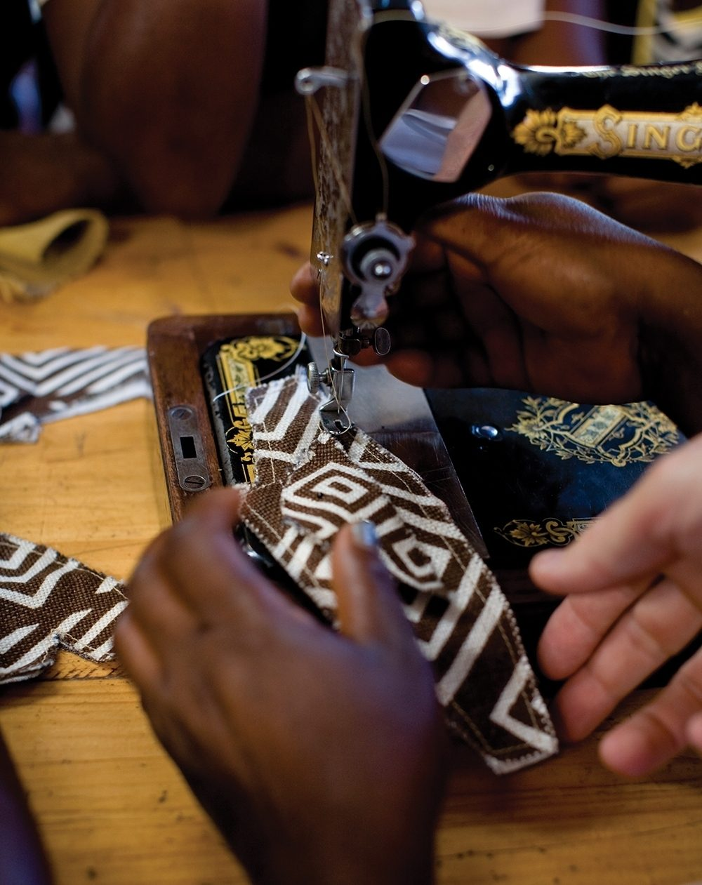 A Ugandan woman sews an upper for a Sole Hope shoe. She is one of 16 shoemakers who earn a living sewing for Sole Hope.