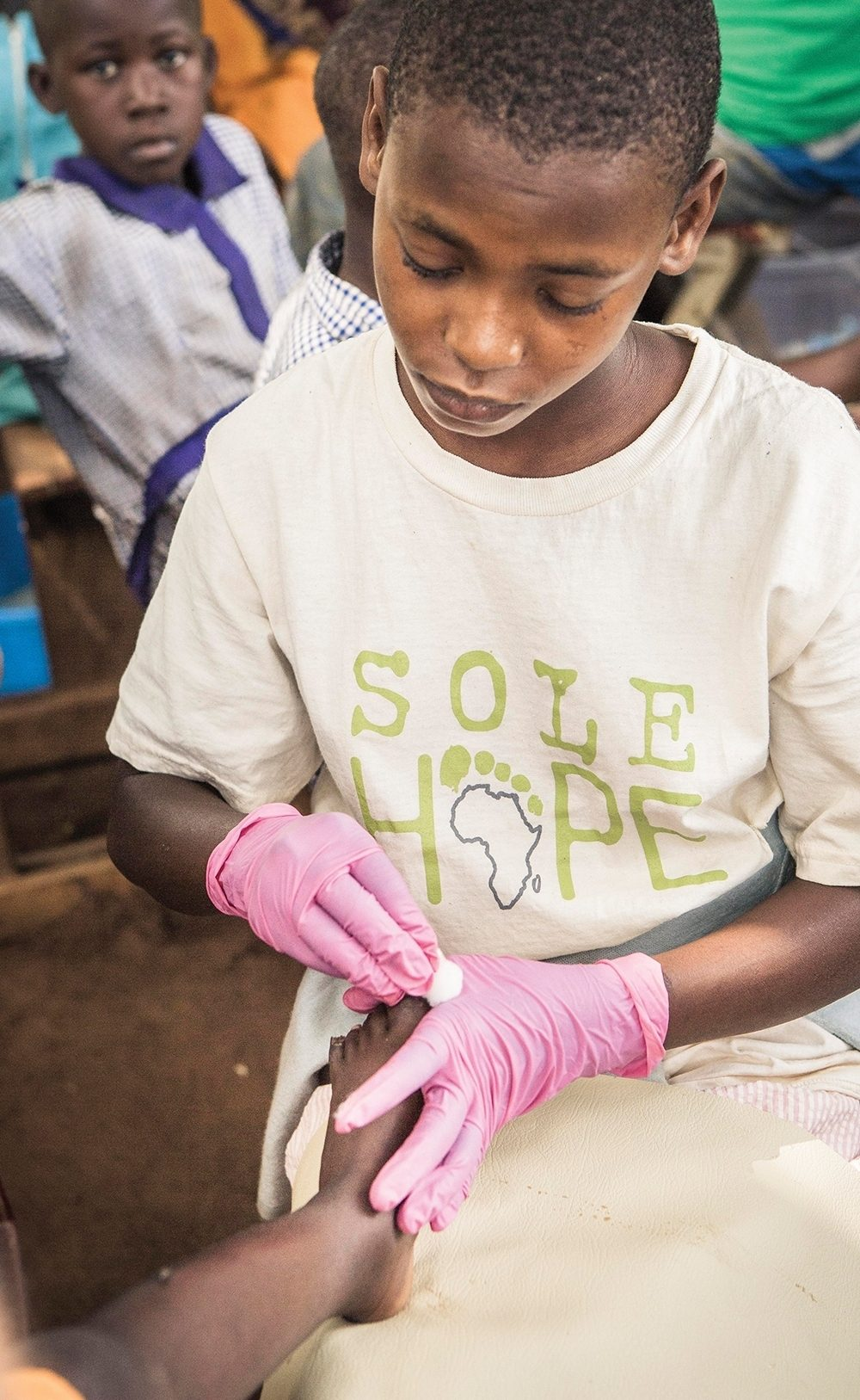 Eleven-year-old Sasha assists at Sole Hope clinics, where she has become an expert at removing jiggers.