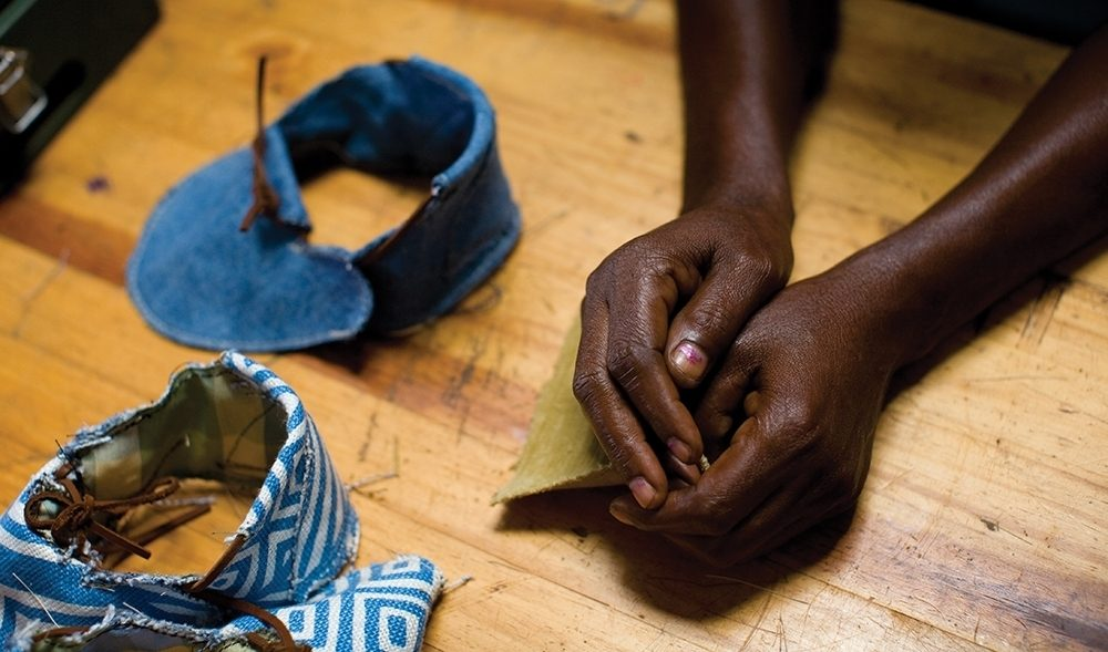 A Ugandan woman sits with uppers for shoes; Sole Hope pays Ugandan widows to assemble shoes.