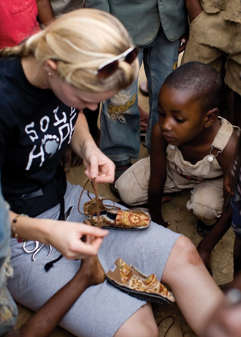 Asher Collie, one of Sole Hope's founders, helps fit a child with a pair of soft-top shoes at the end of a foot clinic.