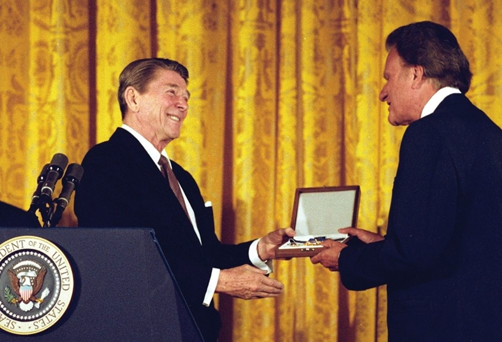 Billy Graham accepts an honor from a friend, President Ronald Reagan.