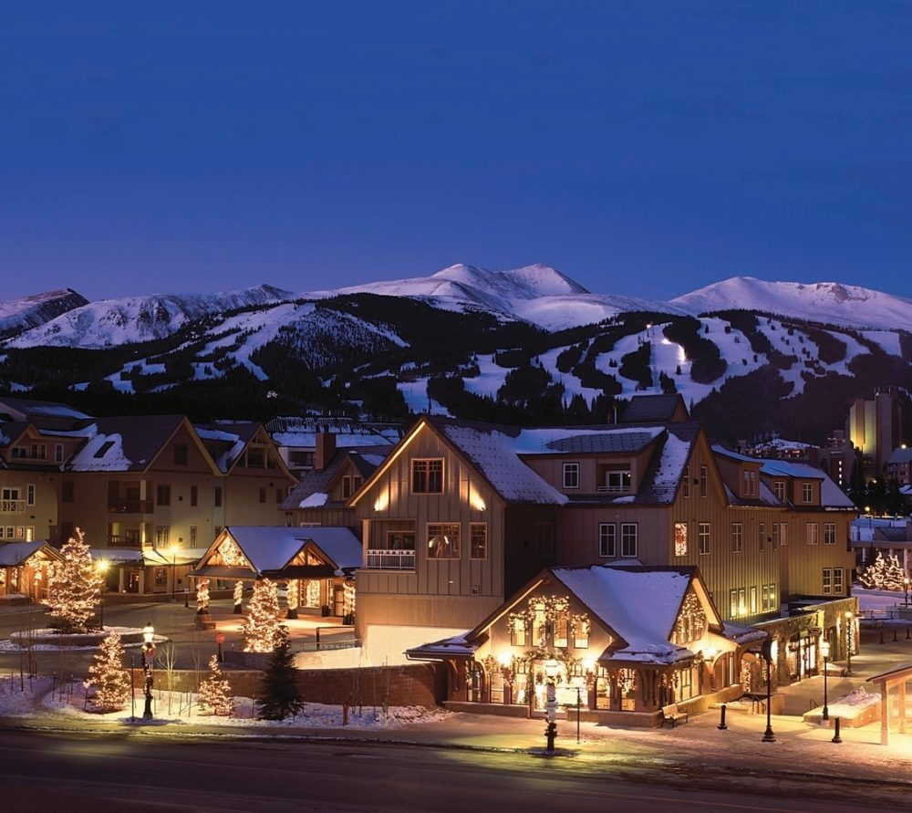 Buildings in front of the Colorado mountains at dusk