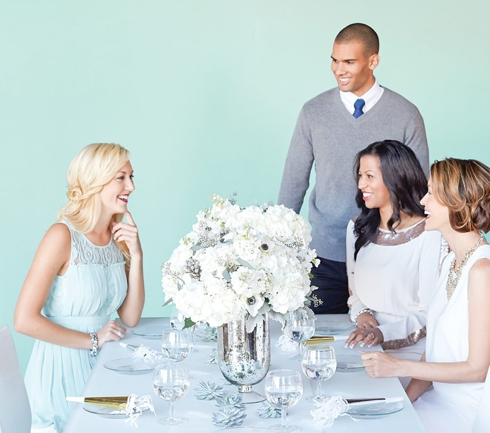 Guests gather around a table for a New Year's Eve party