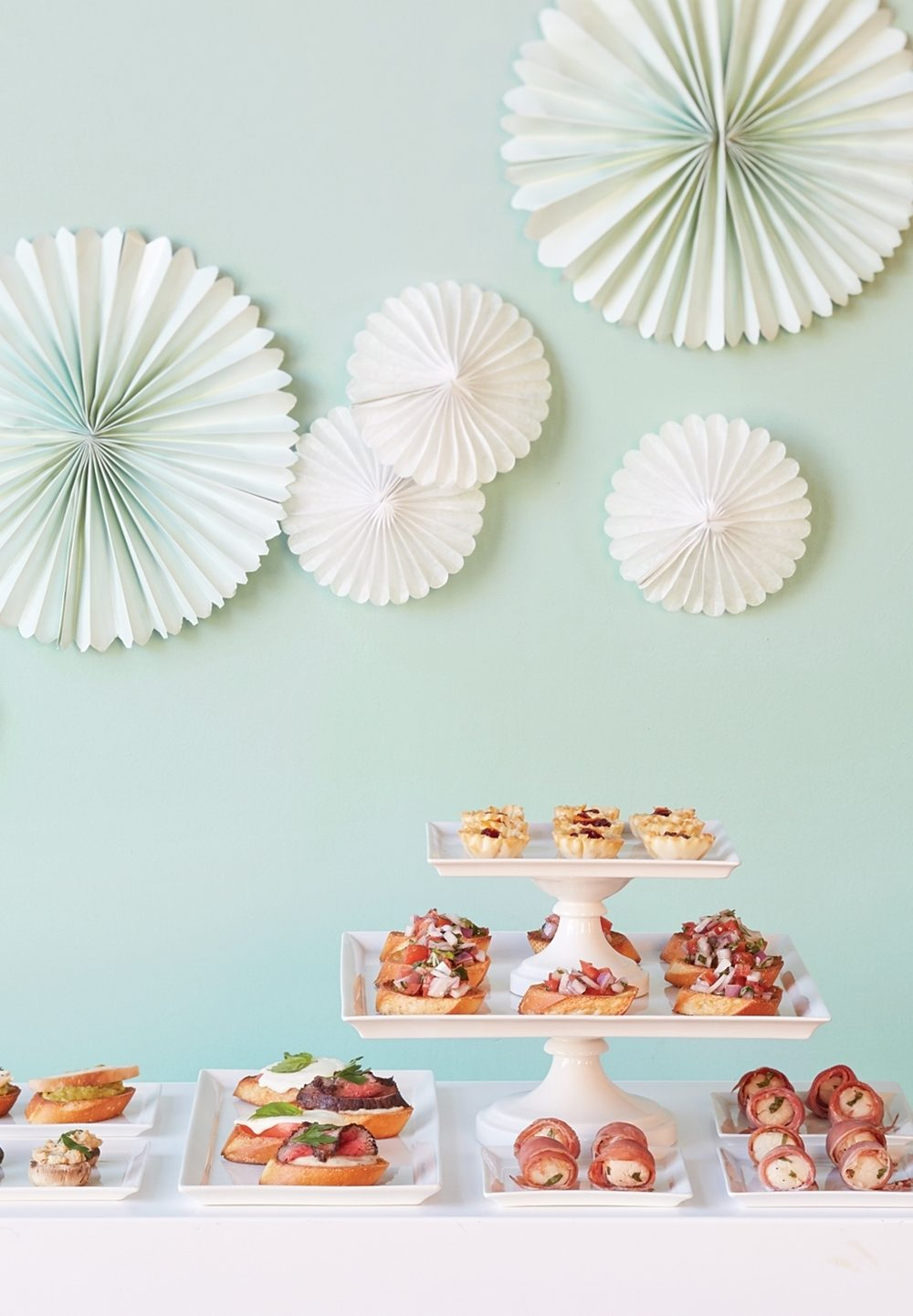 A buffet of finger foods and paper fan decorations